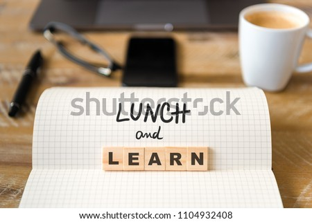 Closeup on notebook over wood table background, focus on wooden blocks with letters making Lunch and Learn text. Concept image. Laptop, glasses, pen and mobile phone in defocused background Royalty-Free Stock Photo #1104932408