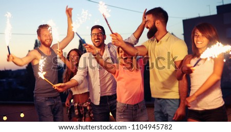Happy friends lighting sparklers and enjoying freedom #1104945782