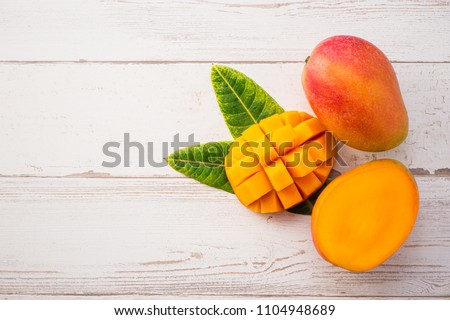 Fresh and beautiful mango fruit with sliced diced mango chunks on a light wooden background, copy space(text space), blank for text, topview. #1104948689
