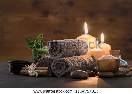 Brown towels with bamboo and candles for relax spa massage and body treatment. Composition with candles, spa stones and salt on wooden background. Spa and wellness setting ready for beauty treatment.  #1104967013