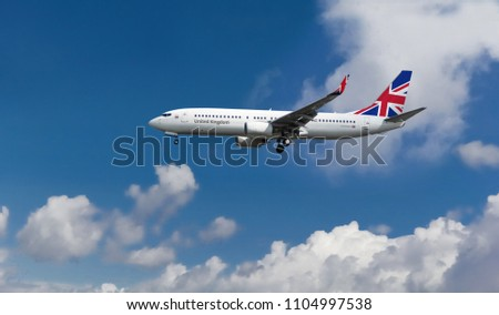 Commercial custom passenger aircraft with British flag on the tail. Blue cloudy sky in the background Royalty-Free Stock Photo #1104997538
