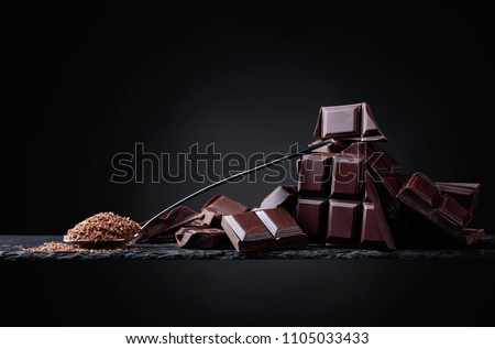 Broken black chocolate pieces and chocolate chip in small spoon on black  background. Copy space. #1105033433