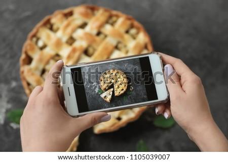 Woman taking photo of tasty homemade apple pie, closeup