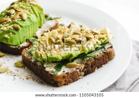 Healthy avocado toasts for breakfast or lunch with rye bread, sliced avocado, arugula, pumpkin and sesame seeds, salt and pepper. Vegetarian sandwiches. Plant-based diet. Whole food concept.