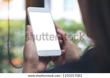 Mockup image of woman holding and using a white mobile phone with blank desktop screen in cafe #1105057082