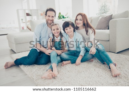 Portrait of lovely cheerful family with two kids in casual outfits sitting on carpet near sofa in modern white livingroom looking at camera. Domicile domestic lifestyle rest relax leisure concept #1105116662