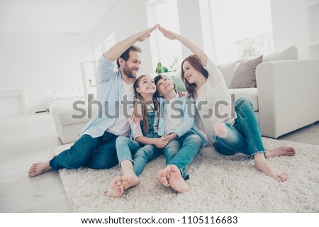 New building residential house purchase apartment concept. Stylish full family with two kids sitting on carpet, mom and dad making roof figure with hands arms over heads #1105116683
