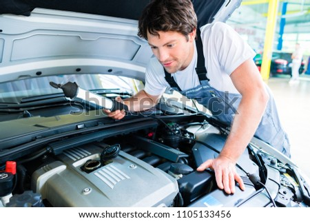 Auto mechanic working on car in service workshop #1105133456