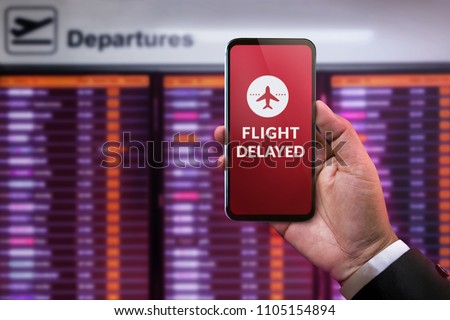 Modern Technology in Travel Concept. Flight Delayed on Smartphone Screen. Businessman using Mobile Phone in front of Departures Board to Re-Checked Flight Information in Airport Royalty-Free Stock Photo #1105154894