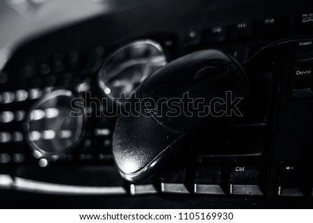 Close up of reading glass and a ball pen with a mouse on keyboard. #1105169930