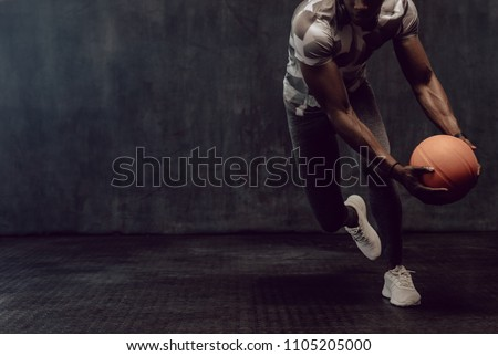 Athletic man training with a basketball. Man working out holding a basketball in hand. Royalty-Free Stock Photo #1105205000