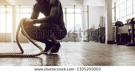 Man sitting on his toes holding a pair of battle ropes for workout. guy at the gym working out with fitness rope. #1105205003