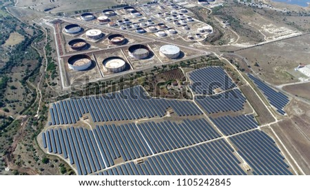 Aerial picture of oil depot and photovoltaic power station also known as solar park is large-scale photovoltaic system designed for the supply of merchant power into the electricity grid