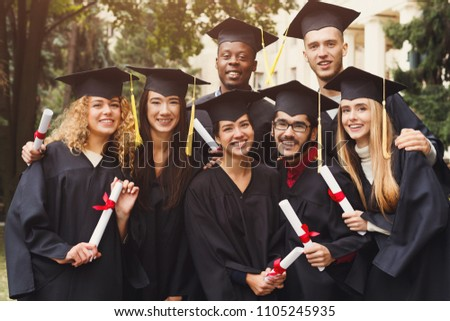 Multiethnic students taking group photo to celebrate their graduation day, copy space. Education, qualification and gown concept.