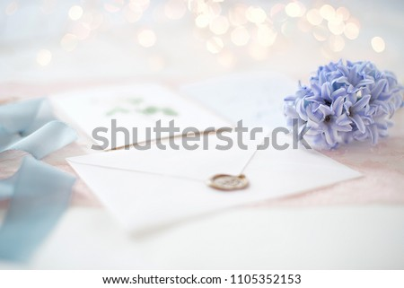 wedding invitation card as a decorated letter with blurred lights on background bokeh