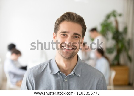 Portrait of casual smiling Caucasian male worker laughing looking at camera, positive employee posing for company business catalogue with colleagues at background, having photo shoot in office Royalty-Free Stock Photo #1105355777