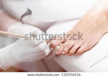 Close up of professional painting by white and glossy acrilyc paint nails on foot. Specialist in beauty salon making french pedicure for female client. Relaxing at beauty salon, caring about nails. #1105356116