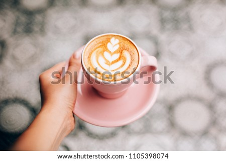 Female hand with pastel pink cappuccino cup with latte art. Vertical moody shoot of coffee