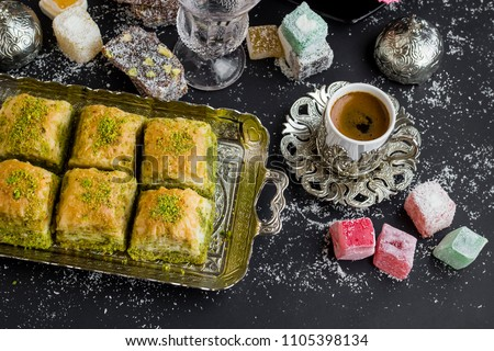 Traditional Turkish Pastry Pistachio Baklava,on vintage tray with coffee and delights.Above view.Conceptual image of celebrations. Royalty-Free Stock Photo #1105398134