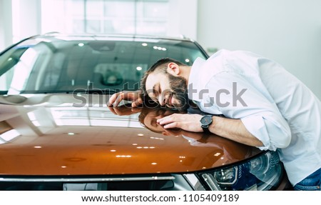 Dreams come true today. Happy handsome bearded man buying a car in dealership #1105409189