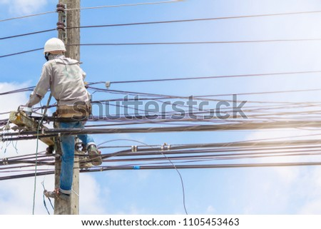 The electrician was climbing up the power poles to perform maintenance work on a protective suit, and a white helmet that protected the head from falling off of tools on a bright blue sky background. #1105453463
