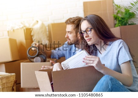 Casual girl with man sitting at home and packing stuff into carton boxes while relocating to new apartment.  #1105480865