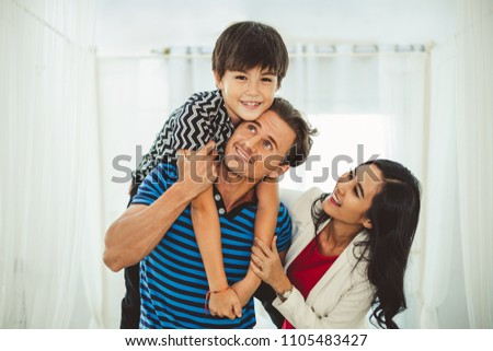 Portrait happy family father, mother and son, child boy playing together in bed room #1105483427