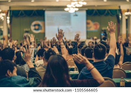 Rear view of Audience showing hand to answer the question from Speaker on the stage in the conference hall or seminar meeting, business and education concept #1105566605