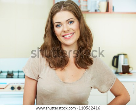 Portrait of young woman with arms crossed standing against kitchen interior background. #110562416