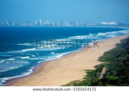 Empty Umhlanga beach shoreline ocean and waves against blue sky City skyline coastal landscape in Durban, South Africa. #1105654172
