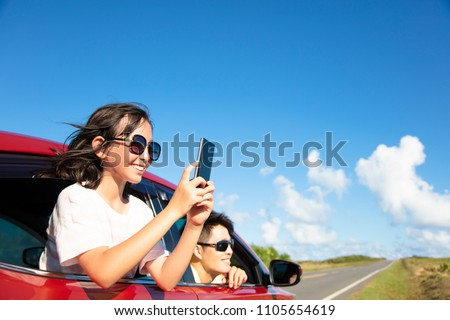 Happy family enjoy road trip taking picture by smart phone