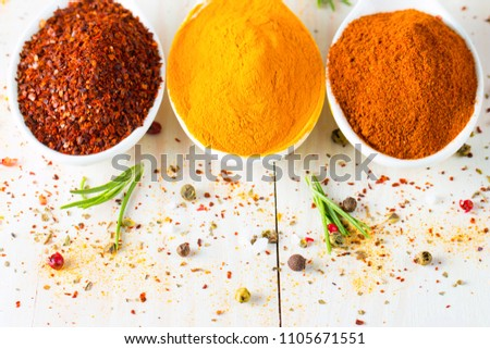 Spices in Wooden spoon. Herbs. Curry, Saffron, turmeric, rosemary, cinnamon, garlic, pepper, anise on wooden rustic background. Collection of spices and herbs. Salt, paprika. Copy space. Top view. Ban #1105671551