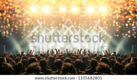 Concert stage with cheerful fans, lens flare and distress effects are visible #1105682801