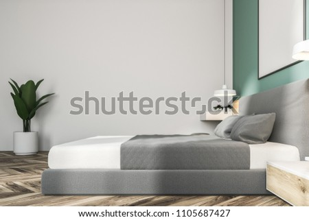 White and green bedroom interior with a wooden floor, a king size bed and a frame vertical poster hanging above it. 3d rendering mock up #1105687427