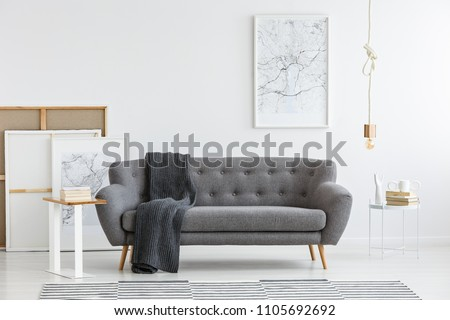 Scandi living room interior with grey, big sofa in the center and modern picture on the wall Royalty-Free Stock Photo #1105692692
