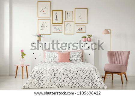 Feminine bedroom interior with a double bed with dotted sheets, armchair, art collection and plants #1105698422
