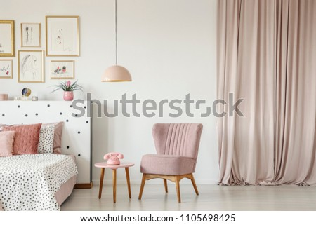 Armchair next to a coffee table with a phone in bedroom interior with a double bed, paintings, lamp and curtain