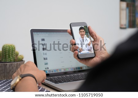 Patient listening to friendly doctor via mobile smartphone at home or office, telemedicine, e health. People watching friendly doctor on health channel internet live broadcast, medical online concept #1105719050