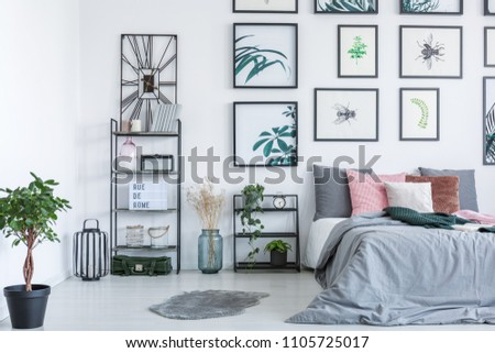 Real photo of a bed standing next to the shelves with ornaments and plants in bedroom interior with paintings on a wall #1105725017