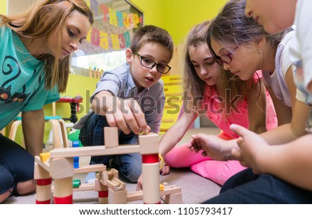 Low-angle view of a dedicated kindergarten teacher helping children with the construction of a wooden train circuit during supervised free playtime #1105793417