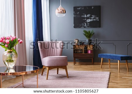 Real photo of a pink armchair standing on a rug and under a lamp in spacious living room interior, next to a table with flowers and in front of a shelf next to a grey wall with dark painting #1105805627