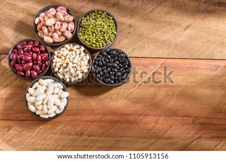 Variety of grains - pinto, black, mung, white, and chickpeas on wooden background #1105913156