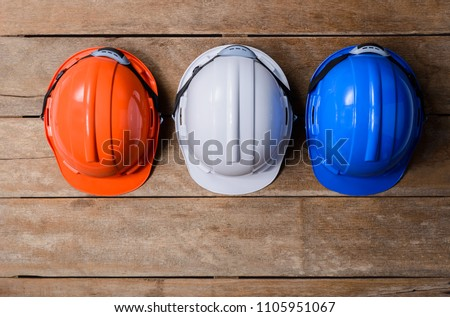 Orange, White and Blue protective safety helmet on old wooden background. safety first concepts #1105951067