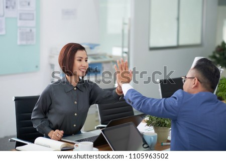 Cheerful Asian managers sitting opposite each other and giving high five after successful completion of joint project, interior of open plan office on background #1105963502