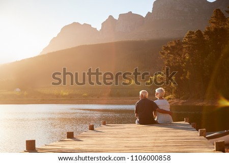 Romantic Senior Couple Sitting On Wooden Jetty By Lake #1106000858