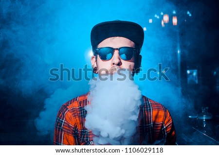 Punk hipster man is smoking a mechanical vape device. Toned image. The concept of popularization of vaping. Vaping man in sunglasses breathes a cloud of steam horizontal #1106029118