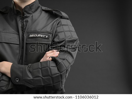 Male security guard in uniform on dark background, closeup Royalty-Free Stock Photo #1106036012