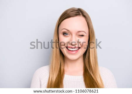 Head shot portrait of charming pretty laughter lovely girl in good mood winking with one eye isolated on grey background #1106078621
