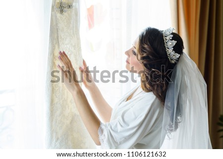 Bride morning preparation. Beautiful bride in white wedding negligee and veil on the background of bedroom #1106121632