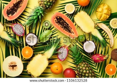 Exotic fruits and tropical palm leaves on pastel yellow background - papaya, mango, pineapple, banana, carambola, dragon fruit, kiwi, lemon, orange, melon, coconut, lime. Top view Royalty-Free Stock Photo #1106132528